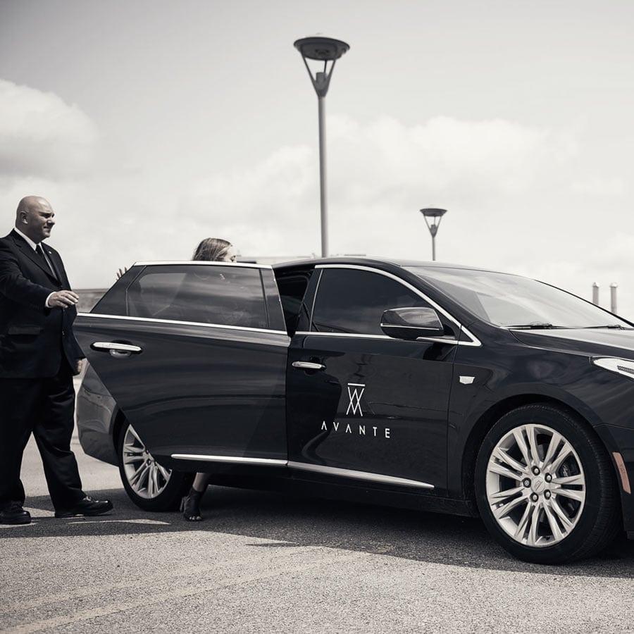 Luxury secure transport, operative opening door escorting executive client.