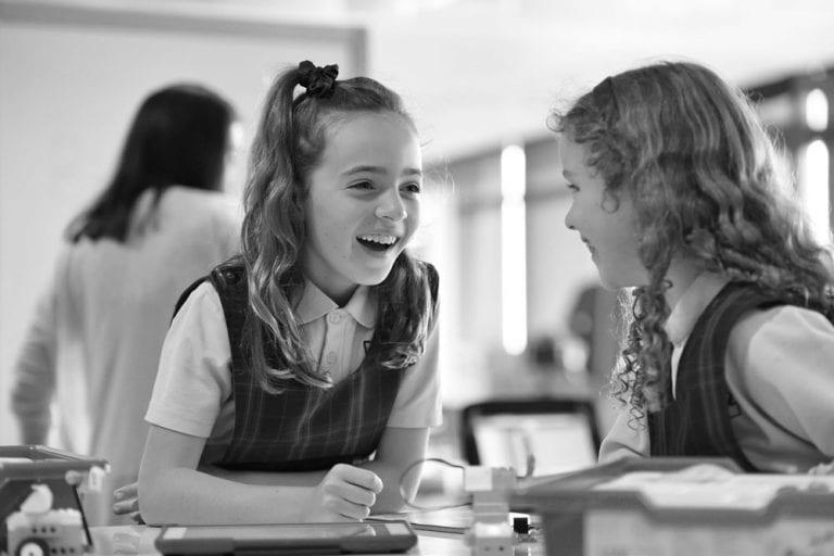 Two kids talking in school in cafeteria