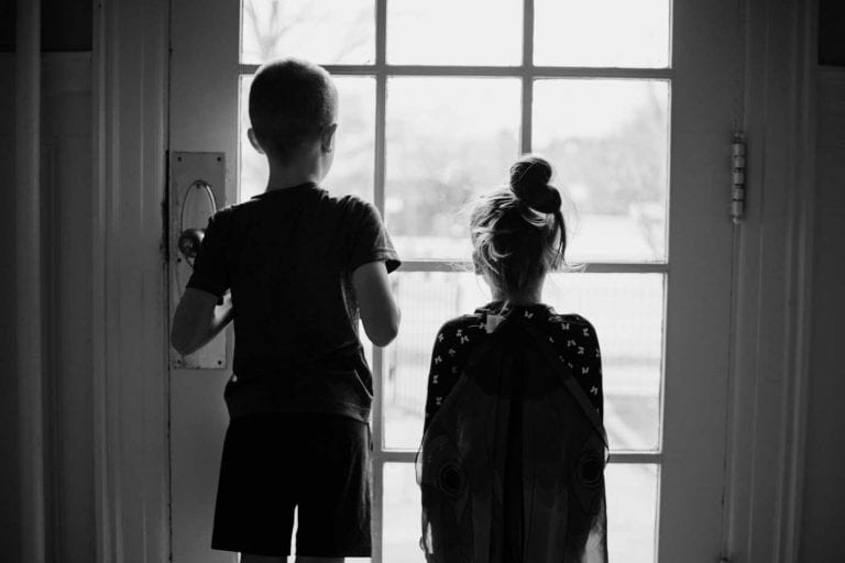 2 childrensilhouette looking outside from the door.