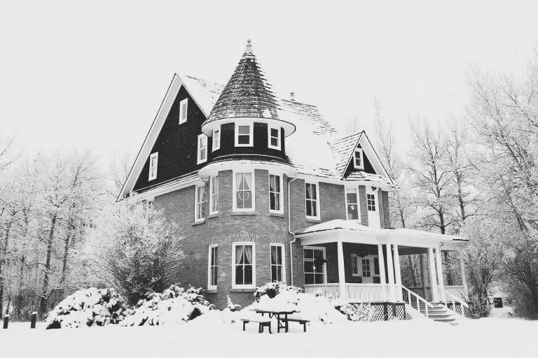 A house covered with a lot of snow.